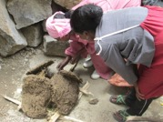 Making Clay Beads – the families are burning the turf to create the clay powder